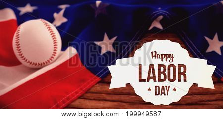 Happy labor day text in banner against baseball on american flag at table