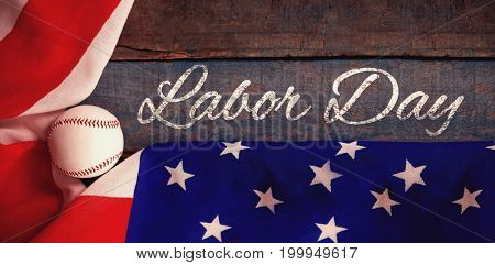 Panoramic shot of labor day text against baseball and american flag on wooden table