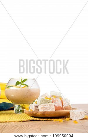 Macro picture of dessert glass filled with thick banana desserts isolated on a white background. Fruit smoothie with decorative mint leaves and dried apricots on a yellow cloth. Copy space.