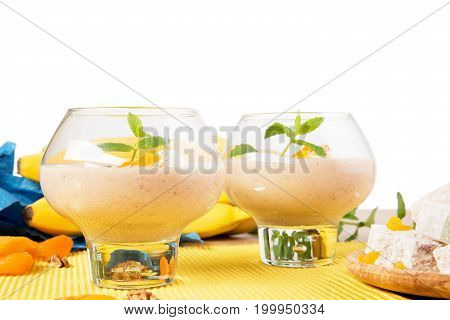 A close-up picture of two dessert glasses filled with thick beverages isolated on a white background. Banana smoothie with decorative mint leaves and dried apricots on a yellow cloth.