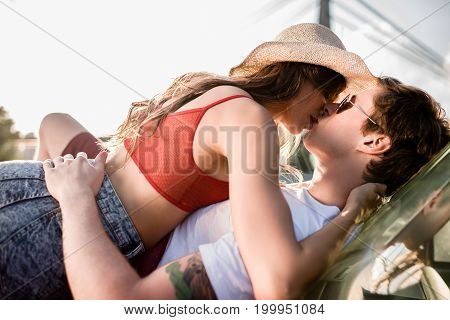 Young Couple Kissing On Car