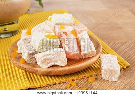 Close-up picture of a plate full of powdered, colorful turkish delight on a yellow fabric on a light table background. Exotic fruity marmalade for a light snack. Beautiful eastern sweets for gourmets.