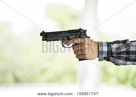 Hand of terrorist holding a gun, close up