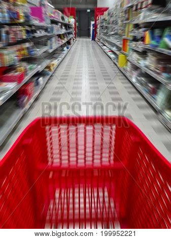 blurred image of a cart trolley in a supermarket aisle with shelves on both sides. for a shopping concept. no people