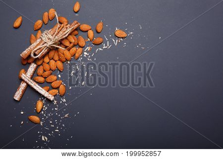 Almond, a bunch of aromatic cinnamon, a component of various dishes, almond butter, cookies, cakes and other sweets and desserts on a dark violet background, copy space.