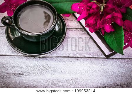 Stack of books, cup of coffee and Rhododendron flowers on wooden background. cover, card. copy space.
