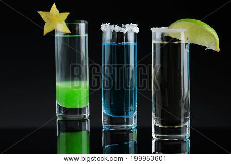 A close-up picture of three bright shots on a black background. Tequila drinks with decorative exotic fruits on a top of shot glasses. Strong alcoholic beverages for crazy parties. Copy space.