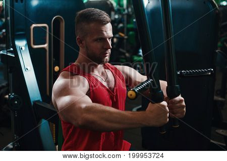 Man Training Hard At Fitness Gym. Man Doing Workout On Fitness Machine At Gym. Gym Trainer Athlete W