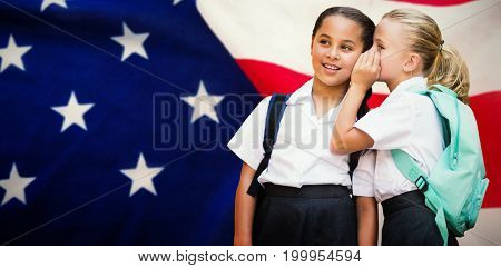 Girl whispering in friend ear against close-up of flag