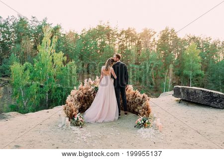 Newlyweds Embracing At The Edge Of The Canyon With Tenderness And Love. Back View. Outdoors Wedding
