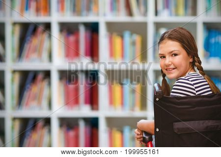 Girl sitting in wheelchair in school against defocused books on shelf