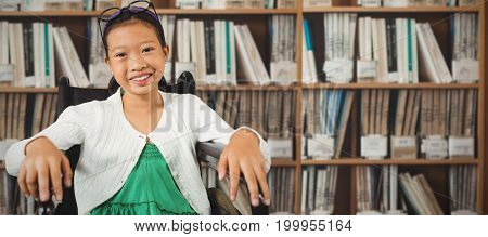 Young girl smiling while sitting on wheelchair against various multi colored books on shelf