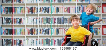 Happy boy pushing friend on wheelchair against multi colored bookshelf in library