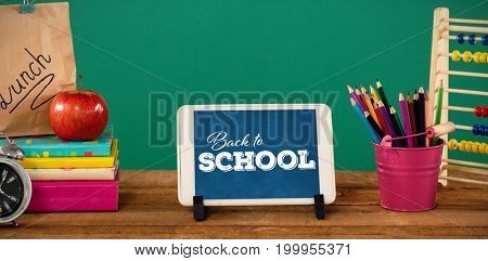 Back to school text over white background against school supplies with digital tablet on wooden table