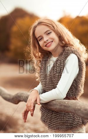Smiling blonde teen girl 14-16 year old wearing stylish clothes posing outdoors. Looking at camera. Autumn season.