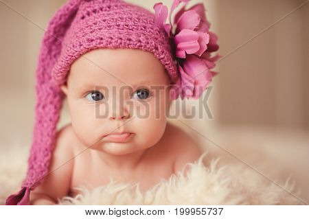 Cute funny baby 2-3 months old wearing pink knitted hat with flower lying in bed. Looking away. Childhood.