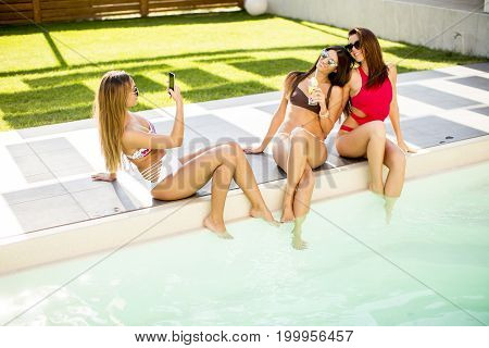 Young Woman Drinking Coctail And Having Fun By The Pool