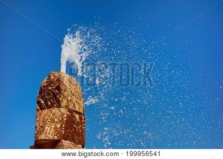 Stone fountain in Lisbon splashing against the blue summer sky.