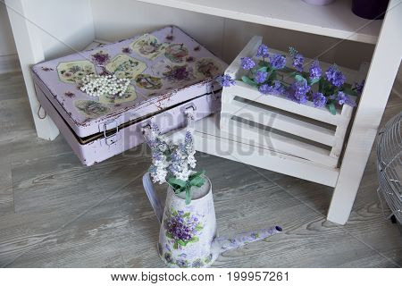 Painted Suitcase And A Watering Can With Flowers