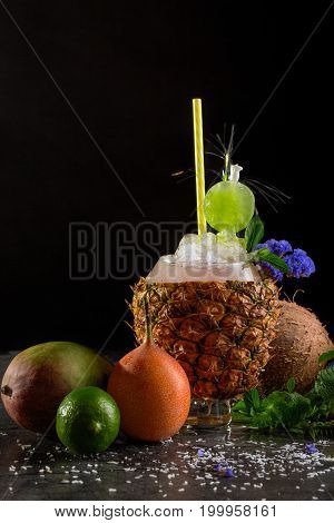 A table with orange pear, green sappy lime, green fresh leaves of mint, a pineapple with a bowl of ice cocktail and coconut on a dark black background.