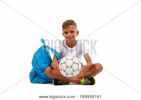 Happy little boy isolated on a white background. A smiling kid with a ball and a blue satchel sitting on the ground in a yoga pose. Lucky schooler with a soccer ball. School concept.