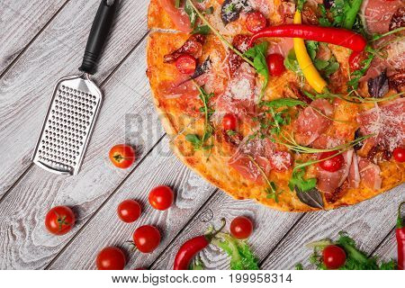 A top-view of a tasty pepperoni pizza next to cherry tomatoes and a metal grate. Tasty dish on a rustic wooden table background. Italian cuisine. Cooking concept. Copy space.