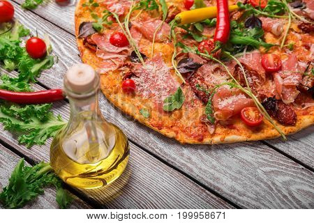 A close-up picture of a tasty margarita pizza with vegetables, a bottle of olive oil and salad leaves. Colorful dish on a rustic table background. Cherry tomatoes and chili pepper. Cooking concept.