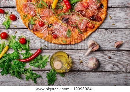 Delicious bright dish on a rustic wooden table background. A view from above on a tasty pepperoni pizza with a bottle of olive oil, garlic, and salad leaves. Italian cuisine. Cooking concept.