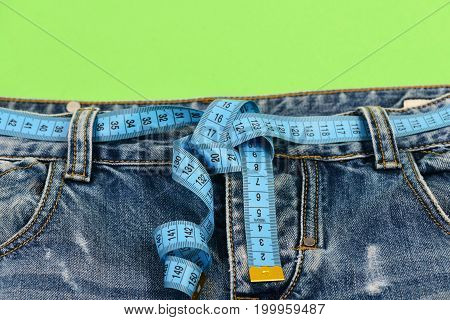 Top part of denim trousers isolated on green background. Close up of jeans with measure tape around waist. Healthy lifestyle and dieting concept. Blue jeans with blue measure tape instead of belt.
