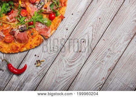 Macro picture of the bright dish on a rustic table background. A view from above on a tasty salami pizza with red hot chili pepper. Italian cuisine. Cooking, baking concept. Copy space.