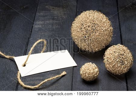 Invitation Card With Golden Deco Balls On Brown Wood