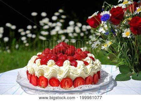Summer objects in a garden - strawberry cake and a bouquet with summer flowers