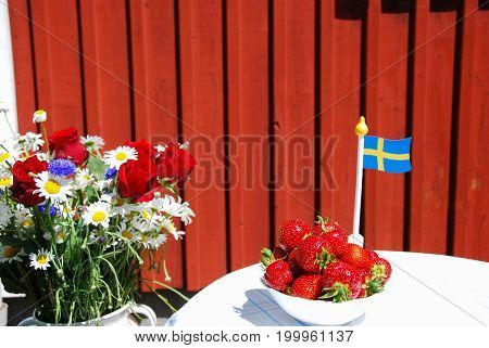Summer decorated swedish table with strawberries flowers and a swedish flag