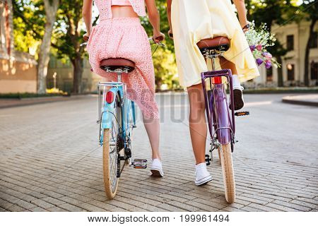 Back view of two girls in dresses riding vintage bicycles outdoors