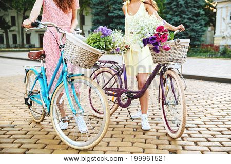 Cropped image of two young women in dresses with retro bicycles on a city street