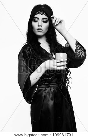 pretty woman or cute sexy girl with long brunette hair in nightie dressing gown black color with lace holds coffee or tea cup isolated on white background