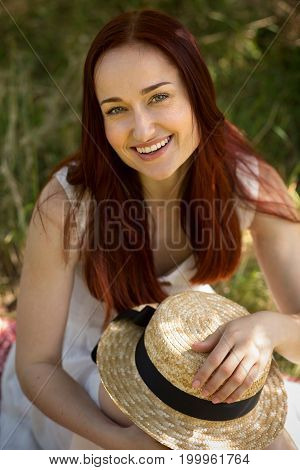 Charming red haired woman enjoying nature outdoors. Young beautiful female holding hat in her hands.