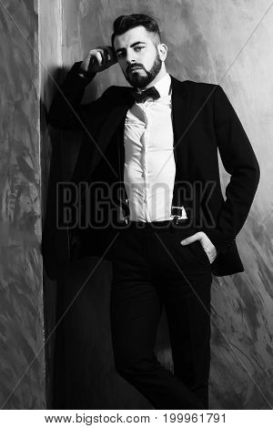 bearded man long beard brutal caucasian hipster with moustache in black elegant suit with bow-tie posing with serious face on brown studio wall background