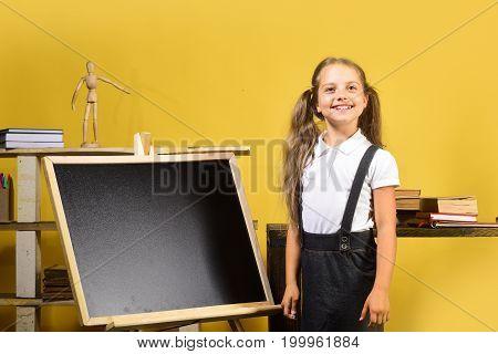 Girl Near Blank Blackboard, Copy Space. Kid And School Supplies