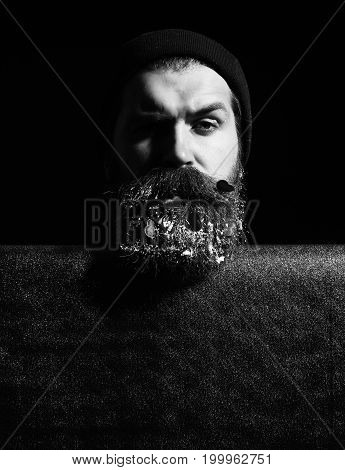 handsome bearded man or guy in winter hat with fashionable mustache on serious face and red decorated hearts with snow in beard near blue paper on black background copy space