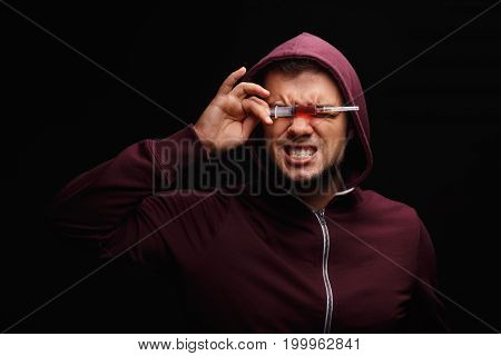 Expressive guy in a dark red hoodie with a drug syringe on a black background. An obsessed with drugs freak suffering from deadly addiction. Youth in need of treatment of drug cravings and addiction.