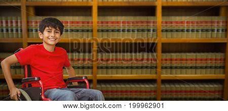 Portrait of boy sitting in wheelchair against bookshelf in school