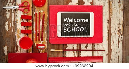Welcome back to school text against white background against school supplies with digital tablet and apple on wooden table
