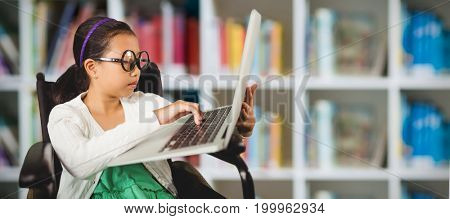 Young girl typing on laptop while sitting against defocused books on shelf