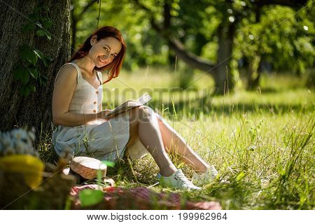 Summer garden, girl sitting on grass, enjoying nature. Attractive foxy woman reading book sitting in garden with her back close to tree.