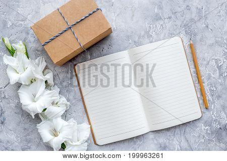 Celebration accessories. Box in kraft paper and notebook on grey stone table top view.