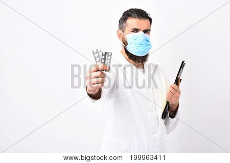 Man with stylish haircut holds black folder offering pills. Medical worker wears blue medical mask. Physician with beard dressed in lab gown isolated on white background. Medicine and health concept