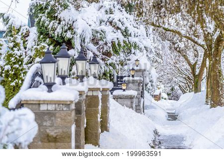 stone fence with lamps and snow