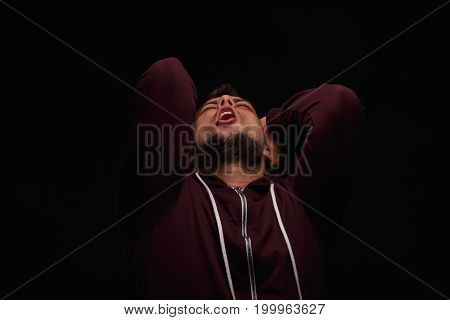 Helpless, mentally ill young man holding his head in disappointment on a black background. Stressed, tired student in a loose dark hoodie. Anxiety, depression, anger issues and self-loathing concept.