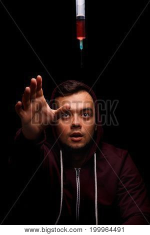 A handsome young man leaning towards syringe with antibiotics. Sick guy in a red hoodie stretches out his hand towards drugs on a black background. Professional treatment and healthcare concept.